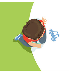 Little boy sitting on his knees and drawing a car vector