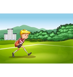 Boy playing rugby in the field vector