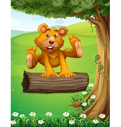 A bear playing with the trunk under the tree vector image vector image
