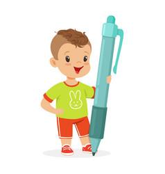 cute smiling little boy holding giant blue pen vector image vector image
