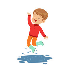 Cute little boy playing on a puddle wearing rubber vector