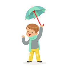 cute little boy holding umbrella playing in the vector image