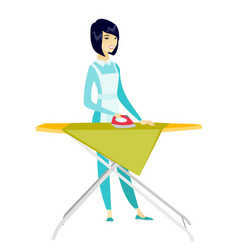 Asian maid ironing clothes on ironing board vector