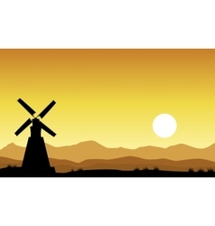 Silhouette of windmill on yellow sky vector