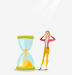 Desperate business woman looking at hourglass vector