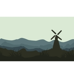 Silhouette of windmill on mountain backgrounds vector