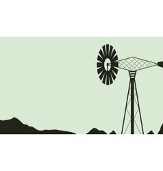 Silhouette of windmill on farm landscape vector