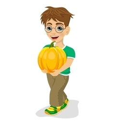 Cute little boy carrying a large pumpkin smiling vector