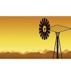 Silhouette of windmill at sunrise vector