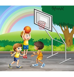 Three children playing basketball at the court vector image