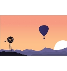 Silhouette of windmill and air balloon scenery vector