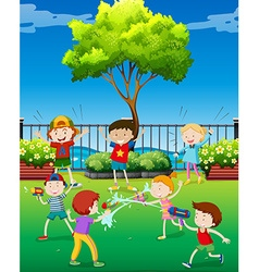 Children playing water gun in the park vector