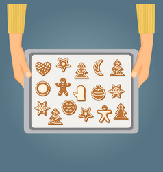 hands holding baking tray with christmas cookies vector image
