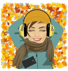 Woman listening to music lying on autumn leaves vector