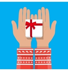 Hand holding white gift box with red bow vector image