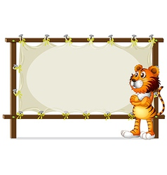A tiger standing beside a wooden frame vector image