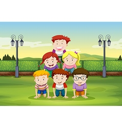 Kids doing human pyramid in the park vector