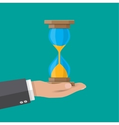 Human hand holds old style hourglass clocks vector image