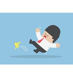 Businessman slipping on a banana peel vector image