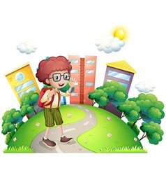 A schoolboy waving while walking at the road vector image vector image