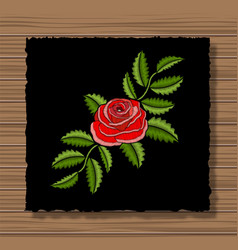 embroidery rose on a dark flap cloth and wooden vector image vector image