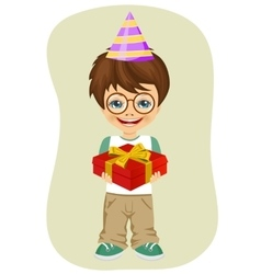 boy with party hat holding birthday gift vector image