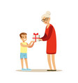 grandmother giving gift box to her happy grandson vector image