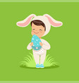 sweet little baby in a white bunny costume holding vector image