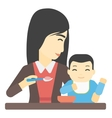 Woman feeding baby vector image