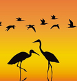Storks in the middle of a reservoir on an orange vector image