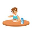 cute boy eating porridge while having breakfast in vector image