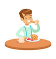 happy boy sitting at the table and eating cookies vector image