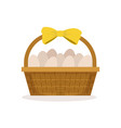 basket with yellow bow full of fresh farm eggs vector image