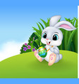 Cute Easter Bunny painting an egg on the Meadow vector image