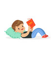 cute little boy lying on a pillow and reading a vector image