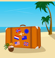 vintage suitcase with flag stickers on beach vector image
