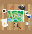 wooden table with paper map planning trip vector image