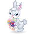 Cartoon Easter bunny holding colourful Easter eggs vector image