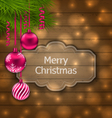 Christmas label with balls and fir twigs on wooden vector image vector image