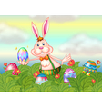 A rabbit with easter eggs in the garden vector image