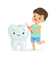 smiling boy brushing a big smiling toorh with a vector image