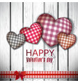 Red cloth handmade hearts on wooden background vector image