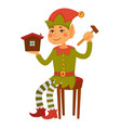 elf sits on stool and builds toy house vector image