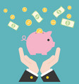 business hand holding piggy bank with flying coins vector image