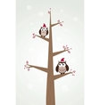 owls couple in christmas hats on the tree branch vector image