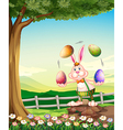 A rabbit juggling the Easter eggs vector image vector image