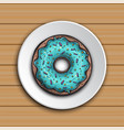 donut with mint glaze on a white plate on the wood vector image