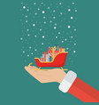 santa claus hand holding sleigh containing a full vector image