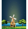 A wooden barnhouse at the river with a windmill vector image
