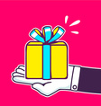 hand holding yellow gift box with blue ri vector image